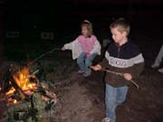 Devon and Blake cooking hotdogs on the fire