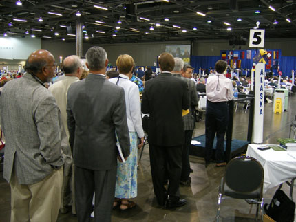 Deputies line up at a mic to speak to resolutions at The General Convention