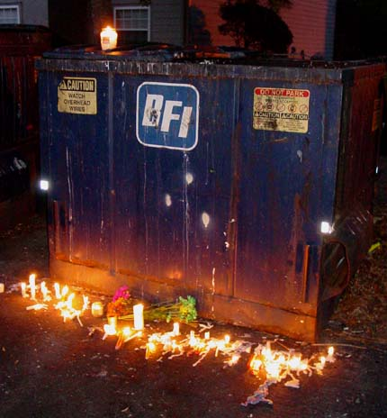 Candles burning in front of a dumpster