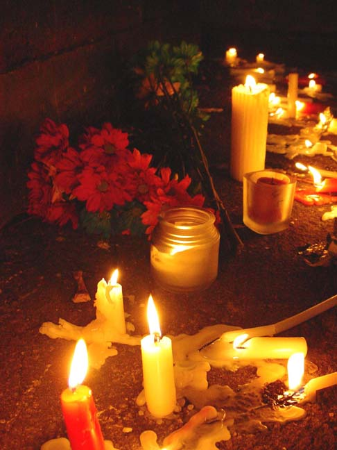 flowers and candles in front of the dumpsters